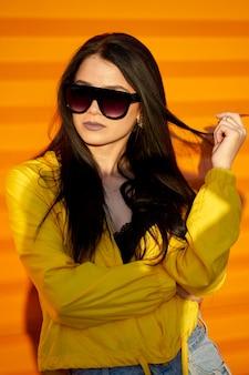 Atractiva chica morena joven inconformista vistiendo ropa juvenil de moda gafas de sol de moda posando sobre fondo de pared urbana naranja.