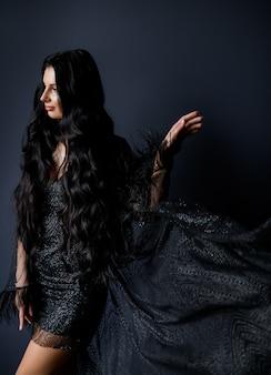 Atractiva chica morena de pelo largo vestida con un vestido negro de lujo en el fondo negro