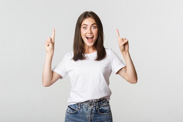 Atractiva chica morena sonriente apuntando con el dedo hacia arriba
