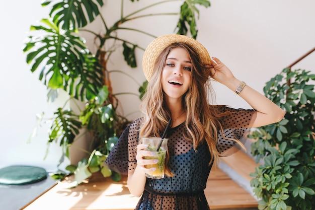 Atractiva chica de pelo largo con sombrero con maquillaje nude de pie con cóctel en la habitación con grandes plantas en macetas