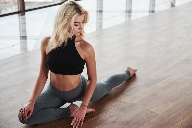 Atractiva chica rubia con buen cuerpo haciendo ejercicios de calentamiento para las piernas