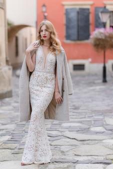 Atractiva chica rubia en elegante vestido beige de noche al aire libre cerca del edificio con pared roja