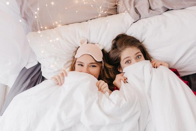 Atractiva chica rubia en máscara de dormir rosa escondida debajo de la manta. foto interior de dos hermanas refinadas bromeando durante la sesión de fotos matutina.