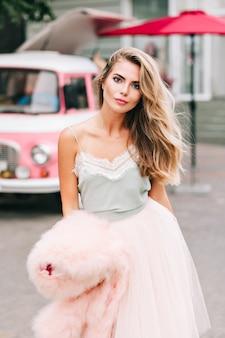 Atractiva chica rubia con el pelo largo en falda de tul en la calle. ella mira a la cámara.