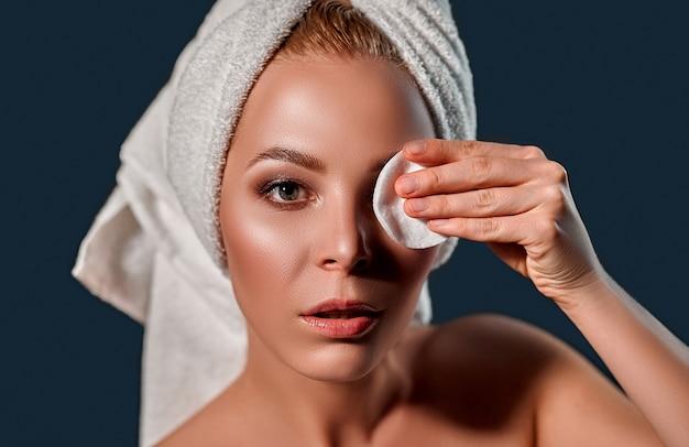 Atractiva chica rubia con piel fresca perfecta aplicando bálsamo en los ojos con almohadilla redonda blanca en la pared negra.