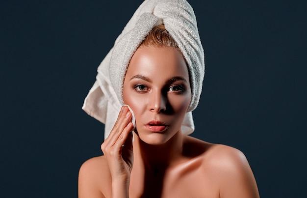 Atractiva chica rubia con piel perfecta aplicando bálsamo en la mejilla con almohadilla redonda blanca en la pared negra.