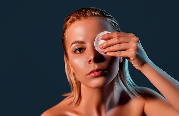 Atractiva chica rubia con piel perfecta aplicando bálsamo en los ojos con almohadilla redonda blanca