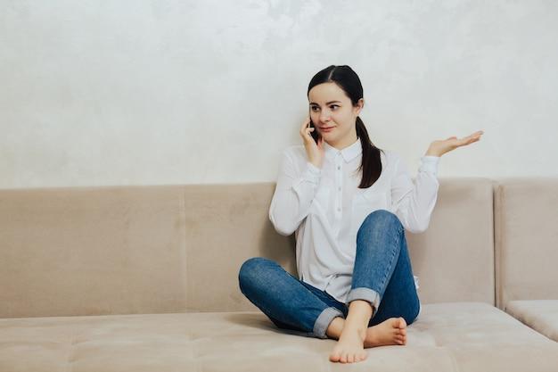Atractiva chica sonriente hablando por teléfono celular mientras está sentado en el sofá beige de la sala de estar.
