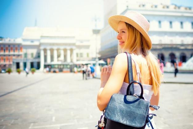 Atractiva chica turista con sombrero con mochila explorando la nueva ciudad de europa en verano