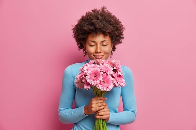 Atractiva y complacida modelo de piel oscura recibe flores como regalo, se para con los ojos cerrados, disfruta de sus gerberas favoritas,