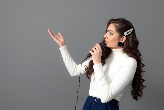 Atractiva conferenciante femenina durante la presentación, sostiene el micrófono y hace algunos gestos, aislado en gris