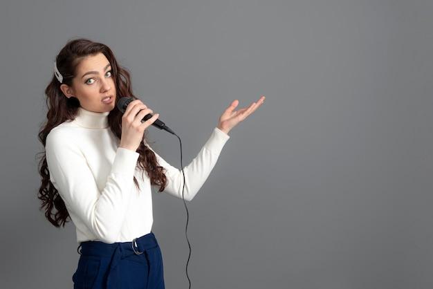 Atractiva conferenciante femenina durante la presentación, sostiene el micrófono y hace algunos gestos