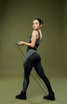 Atractiva dama deportiva en ropa deportiva sosteniendo saltar la cuerda y mirando a la cámara con expresión seria. aislado sobre fondo verde