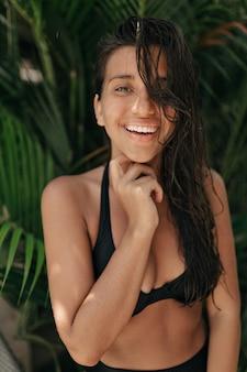 Atractiva dama encantadora expresa felicidad, satificada con resort de verano, vistiendo traje de baño, posando en la jungla. feliz turista viaja al extranjero