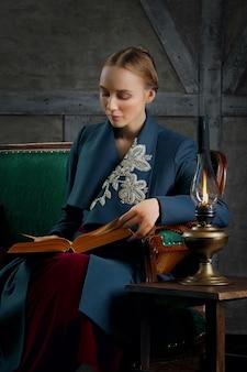 Atractiva dama leyendo libro antiguo cerca de lámpara de keroseno vintage