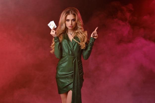 Atractiva dama rubia, maquillaje brillante, elegante vestido verde y joyas. mostrando dos ases, apuntando a algo, posando sobre fondo ahumado colorido, luz de fondo. juegos de azar, póquer, casino. de cerca