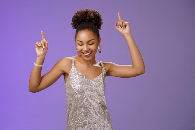 Atractiva y despreocupada estudiante afroamericana diviértase en el baile de graduación en el club nocturno sonriendo encantada con los dedos índices hacia arriba y mirando hacia abajo con alegría, triunfando celebrando las buenas noticias, fondo azul.