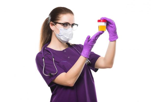 Atractiva doctora caucásica con muestra de orina en sus manos en máscara médica y guantes estériles