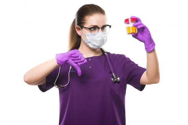 Atractiva doctora caucásica sosteniendo una muestra de orina en sus manos con máscara médica y guantes estériles con el pulgar hacia abajo en blanco