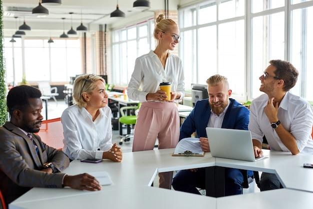 Atractiva ejecutiva jefa agradable discutir ideas de negocios con los empleados