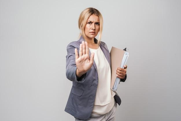 Atractiva empresaria enojada de pelo rubio enojado vistiendo chaqueta que se encuentran aisladas sobre la pared gris, llevando carpetas, gesto de parada