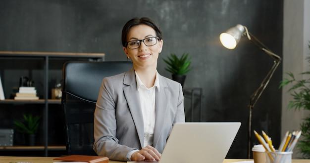 Atractiva empresaria escribiendo en el teclado y mensajes de texto, pensando en el gabinete.