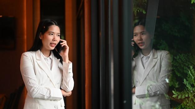 Atractiva empresaria hablando por su teléfono mientras está de pie frente a las ventanas en la oficina.