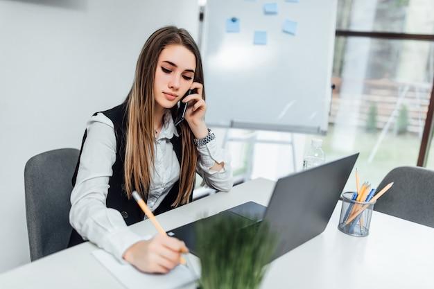 Atractiva empresaria inteligente, propietaria de una gran empresa, tiene una reunión en línea con socios comerciales internacionales, por teléfono.