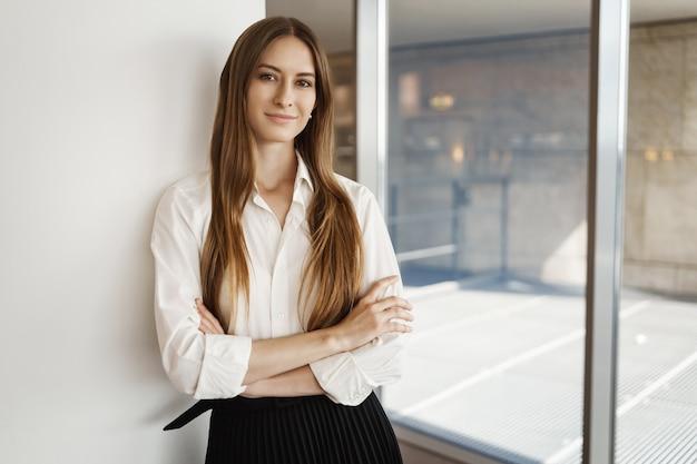 Atractiva empresaria joven satisfecha de pie orgullosa, sonriendo con las manos cruzadas confiado