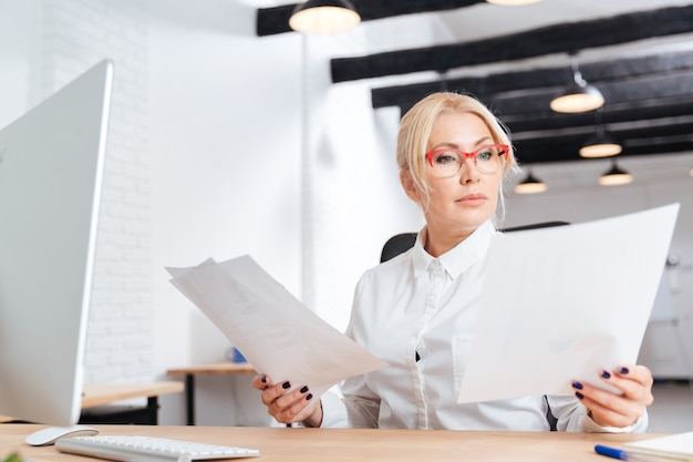 Atractiva empresaria madura pensativa leyendo papeles en office