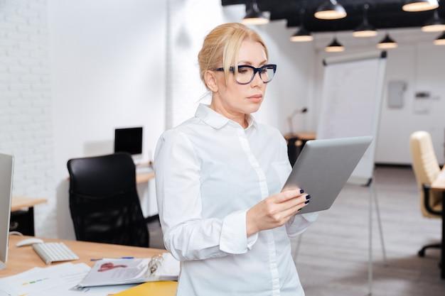 Atractiva empresaria madura de pie en la oficina con tablet pc
