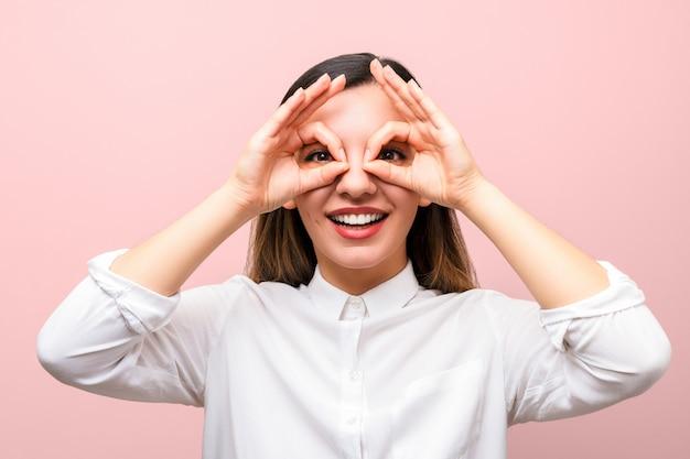 Atractiva empresaria o estudiante con labios rojos en camisa blanca sonriendo y haciendo gafas con los dedos sobre fondo rosa