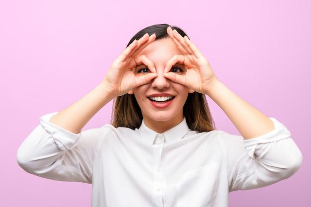 Atractiva empresaria o estudiante con labios rojos en camisa blanca sonriendo y haciendo gafas con los dedos