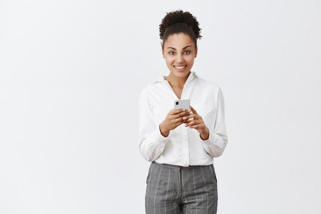 Atractiva empresaria con piel oscura en traje, sosteniendo un teléfono inteligente y mirando con una amplia sonrisa, hablando con el cliente a través de mensajes, esperando un café en la cafetería camino a la oficina por la mañana