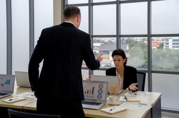 Atractiva empresaria y socio hablando y discutiendo en la mesa de reuniones con tableta presentando gráficos, diagramas y tablas de análisis financiero en pantalla. negociación.