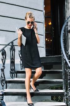 Atractiva empresaria en vestido corto negro bajando escaleras. ella está hablando por teléfono y sonriendo.