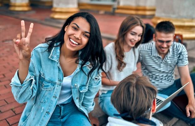 Atractiva estudiante afroamericana se sienta en los escalones cerca del campus con sus amigos y muestra el gesto de libertad.