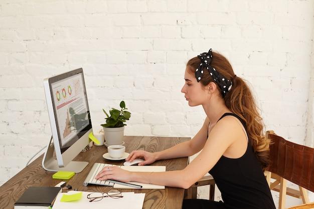 Atractiva estudiante analizando las principales empresas de información financiera para su tesis científica mirando el cuadro financiero en el interior de una casa. la chica decidida que investiga las tareas financieras.