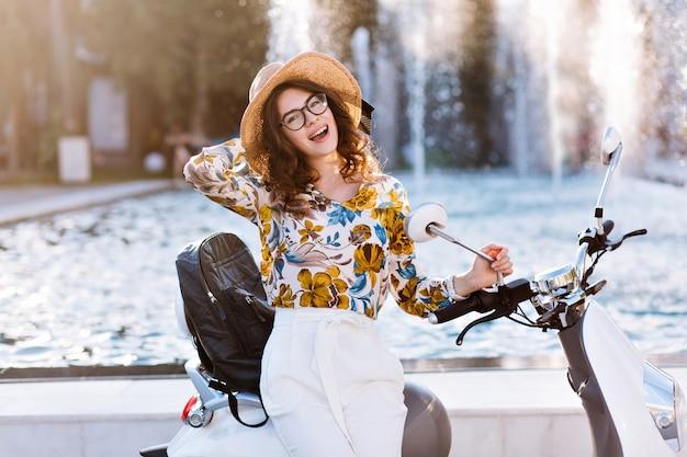 Atractiva estudiante posando juguetonamente con sombrero nuevo tocando su scooter frente a la fuente