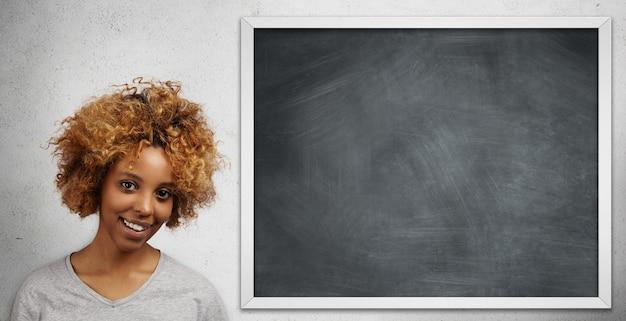Atractiva estudiante universitaria africana con piercing facial presentando su proyecto a la clase de pie en la pizarra en blanco.