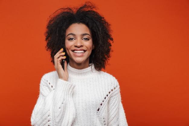 Atractiva joven africana vistiendo suéter hablando por teléfono móvil aislado sobre pared roja