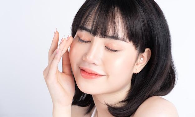 Atractiva joven asiática con piel fresca. cuidado de la cara, tratamiento facial, piel de belleza de mujer aislada en blanco. cosmetología, belleza de la piel y concepto cosmético.
