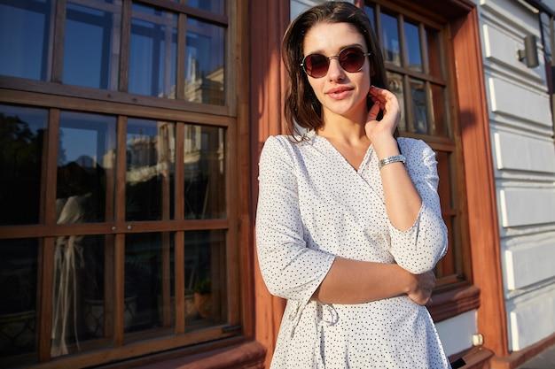 Atractiva joven de cabello oscuro con gafas de sol y un romántico vestido de lunares de pie sobre la escena urbana, tocando suavemente su cuello con la mano levantada y mirando con aire