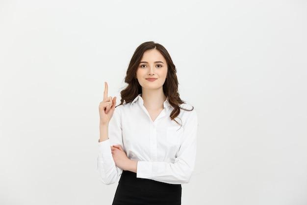 Atractiva joven caucásica sonriendo y apuntando con su dedo índice a la parte superior.