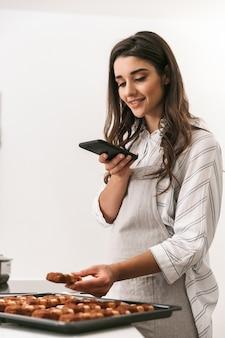 Atractiva joven cocinando sabrosas galletas en una bandeja mientras está de pie en la cocina, tomando una fotografía