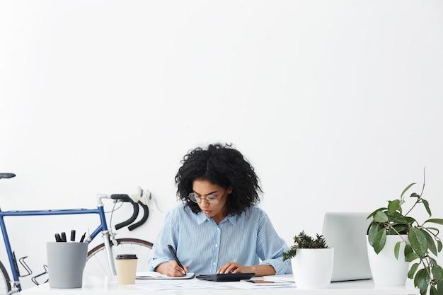 Atractiva joven contadora afroamericana vistiendo camisa azul y anteojos