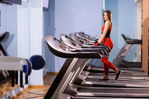 Una atractiva joven corre en una cinta de correr, participa en un gimnasio deportivo