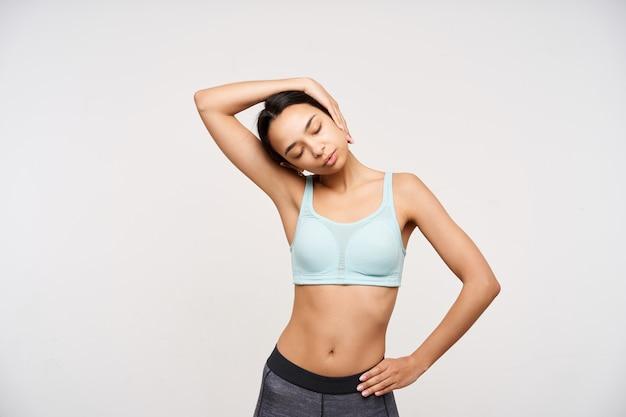 Atractiva joven dama de cabello castaño delgado que mantiene los ojos cerrados mientras hace ejercicios para el cuello y tira de la cabeza con la mano levantada, aislada sobre la pared blanca