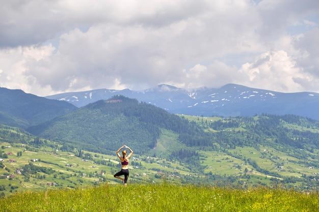 Atractiva joven delgada haciendo ejercicios de yoga al aire libre