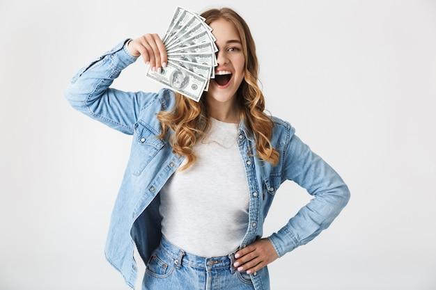 Atractiva joven emocionada que se encuentran aisladas sobre blanco, mostrando billetes de dinero